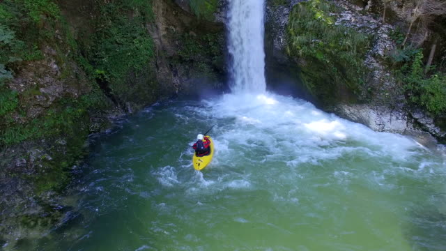 AERIAL: Kayaker paddling towards plunge pool of raging whitewater waterfall video