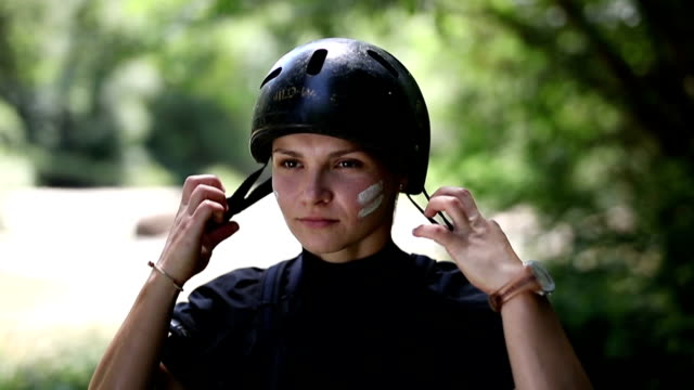 kayaker putting on a helmet Determined female kayaker putting protective helmet on and going out of the frame work helmet stock videos & royalty-free footage