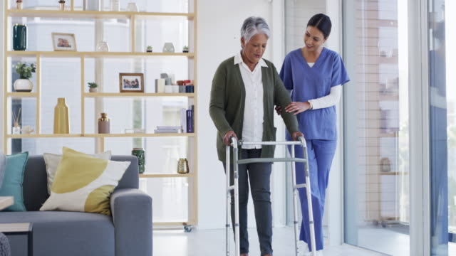 Keep going, you're recovering so well 4k video footage of an attractive young healthcare professional helping a happy senior woman use her walker while indoors orthopedic equipment stock videos & royalty-free footage