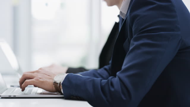 Keep work simpler with wireless technology 4k video footage of a businessman and businesswoman using their laptops in a modern office employee engagement stock videos & royalty-free footage