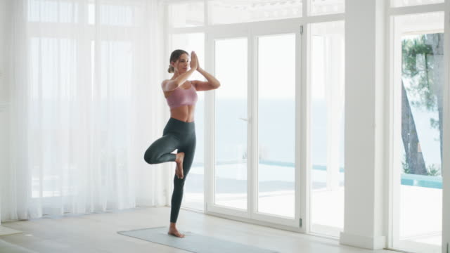 Keep your balance in check 4k video footage of a young woman doing yoga at home yoga stock videos & royalty-free footage
