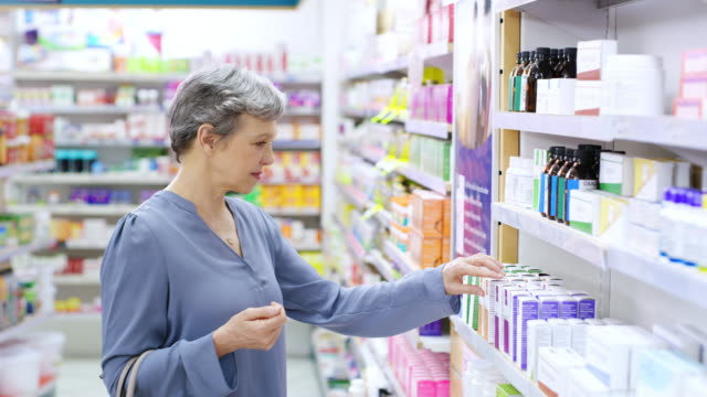 Keeping her health in check with the right medicinal support 4k video footage of a young woman browsing the shelves of a pharmacy pharmacy stock videos & royalty-free footage