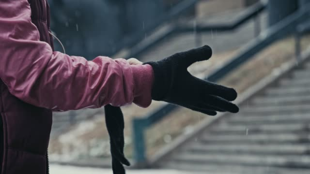 Keeping warm Side view of a woman putting on wool gloves to keep warm on a snowy winter day. She is preparing for fitness training outdoors. glove stock videos & royalty-free footage