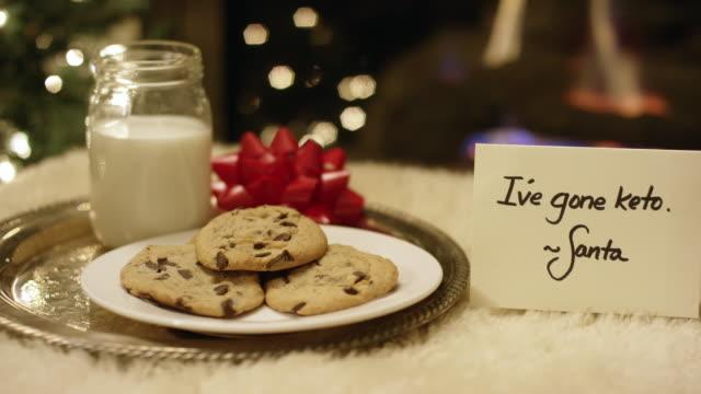 Ketogene Weihnachten: Panning Shot von Santa höflich ablehnen Milch und Kekse, indem eine