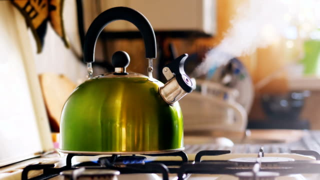 Kettle Boiling On a Gas Stove Kettle boiling on a gas stove. Boiling green kettle boiling with steam emitted from spout. Shallow depth of field. Solar glare from the kitchen window condensation stock videos & royalty-free footage