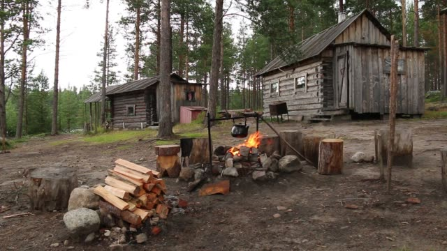 Kettle over campfire near hut in forest video