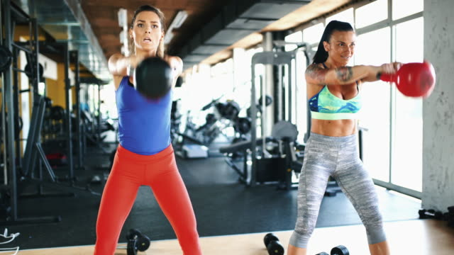 Kettlebell swing exercise. Closeup front view of two mid two women exercising in a gym. They are standing side by side and doing kettlebell swings. Dolly shot, 4k video. swinging stock videos & royalty-free footage