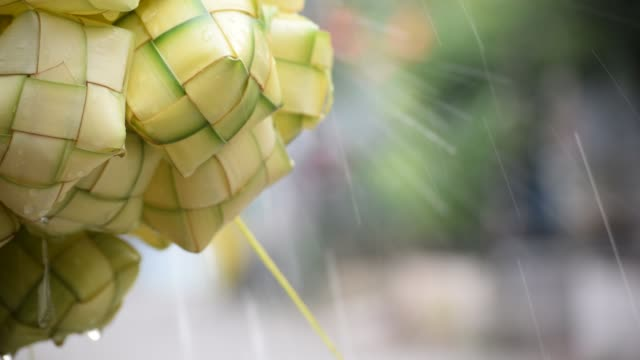 ketupat asian rice dumpling. ketupat is a natural rice casing made from young coconut leaves for cooking rice during eid mubarak eid ul fitr. bokeh background - eid stock videos & royalty-free footage