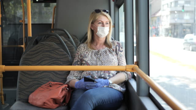 Key employee going to work with face mask and gloves Essential worker in public transportation, traveling to or from work during covid-19 pandemic. Woman is in an empty public bus bus stock videos & royalty-free footage
