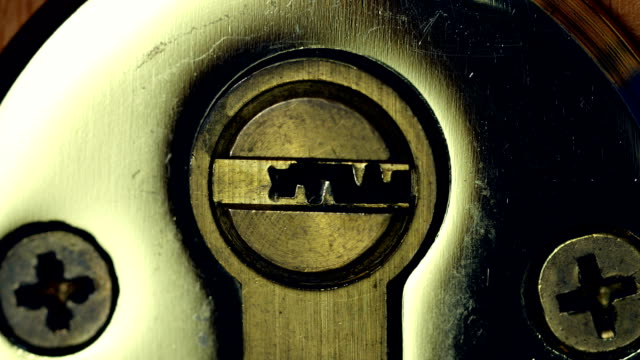 Key in door lock. Close-up of house key sliding into lock and locking door in 4K UHD. Key sliding into lock and locking\ unlocking door. keyhole stock videos & royalty-free footage