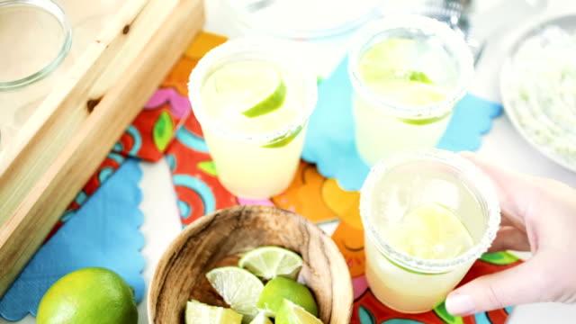 Key lime margarita Key lime margarita garnished with fresh lime in mason jar on colorful paper napkins. margarita stock videos & royalty-free footage