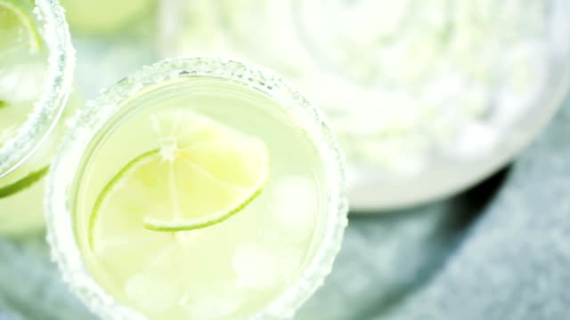 Key lime margarita Key lime margarita garnished with fresh lime and salt in mason jar on metal tray. margarita stock videos & royalty-free footage