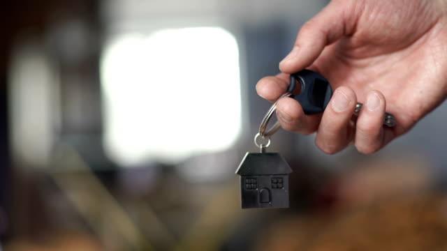 schlüssel für ein neues zuhause. der hintergrund jedoch unscharf - hausschlüssel stock-videos und b-roll-filmmaterial