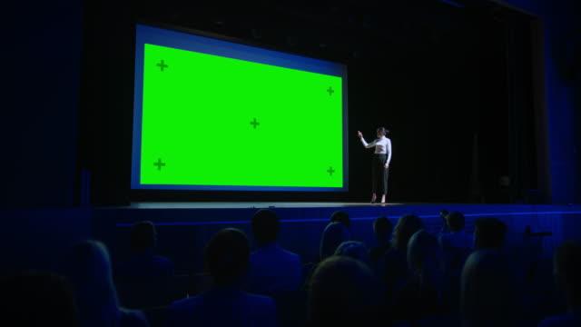 keynote speaker kündigt neues produkt an das applaudierende publikum an, hinter ihrem kino mit green screen, mock-up, chroma key. weibliche ceo zeigt führung auf business live event oder device reveal - zuschauerraum stock-videos und b-roll-filmmaterial