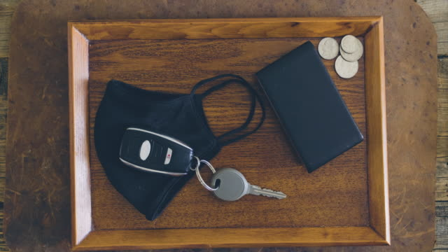 Keys and Mask on a Table A table with keys, wallet, and protective face mask. gripping stock videos & royalty-free footage