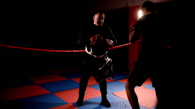 kick boxer practicing with coach in dark gym - sparring allenamento video stock e b–roll