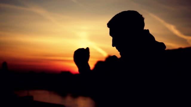 Kick boxer shadow boxing at sunset video