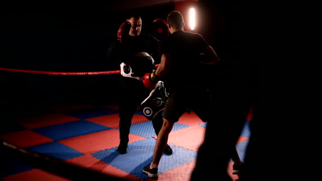 kick boxer training with coach in dark gym - sparring allenamento video stock e b–roll