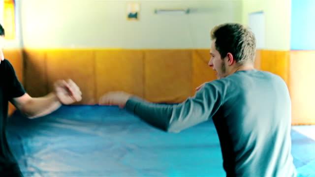 vídeos de stock, filmes e b-roll de kickboxer treinamento no saco de pancada - autodefesa