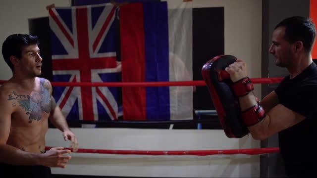 インストラクターとキックボクサートレーニング - スポーツ用品点の映像素材/bロール