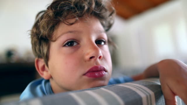 Kid boy at home seated in sofa feeling bored Kid boy at home seated in sofa feeling bored autism stock videos & royalty-free footage