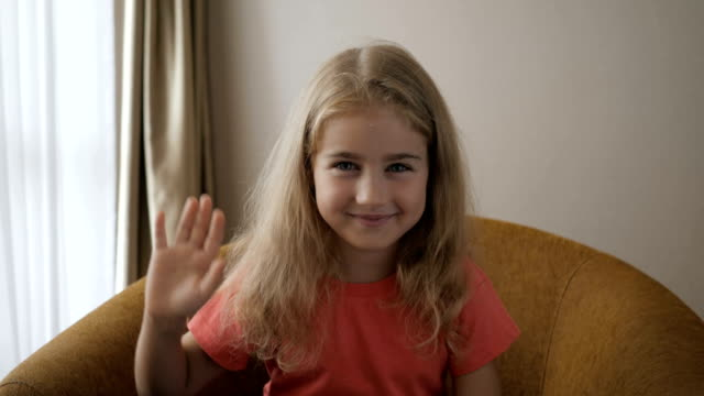 Kid Child Girl Making Online Video Call Recording Vlog Sitting On Sofa , Portrait. Funny Girl Smiling Looking At Camera. Happy Cute Little Vlogger Saying Hello Hi Looking At Camera Talking To Webcam.