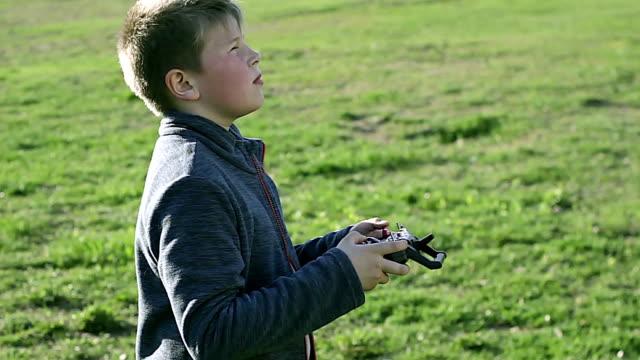 kid controls the drone - telecomando background video stock e b–roll