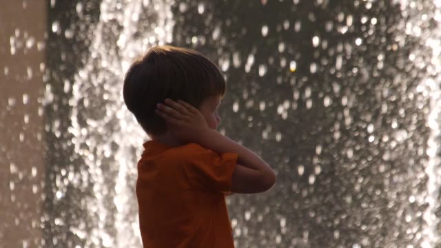 Kid covers his ears with hands to protect from noise. Denial conception. Child negative reaction, emotions on surroundings, environment. Pediatrics background. Psychology concept. Intense sensitivity Boy covers his ears with hands while standing in front of noisy fountain. Sensitive kid to loud noise. Child irritated and worried of loud noise from fountain in the park. Kid's sensitivity disorder autism stock videos & royalty-free footage