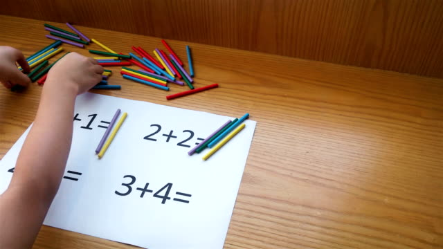 kid doing simple additions by counting numbers of sticks video