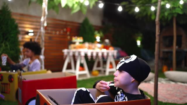 vídeos y material grabado en eventos de stock de niño vestido de esqueleto viendo película en la fiesta del patio trasero de la película de halloween - halloween covid
