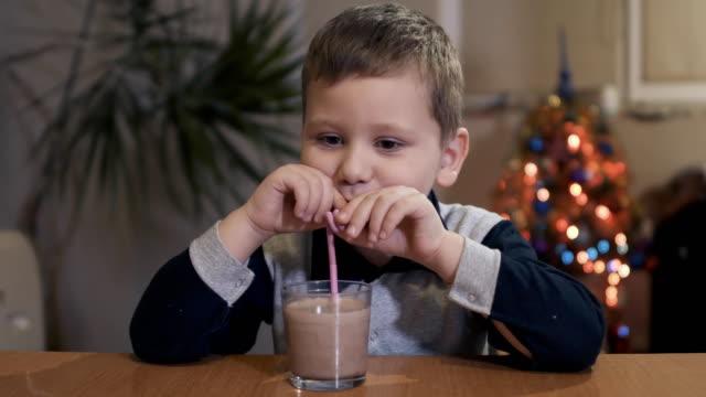 vídeos de stock e filmes b-roll de kid drinking a tasty drink through a straw at home - cacau em pó