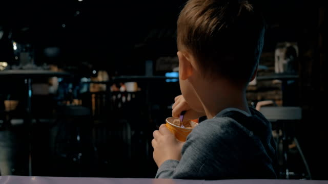 Kid eating chocolate ice-cream in cafe video