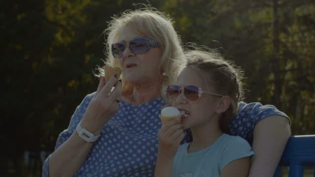 Gosse manger manger icecream avec grand-mère en plein air - Vidéo