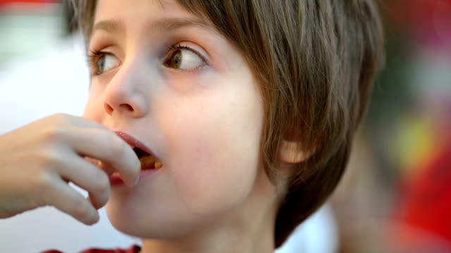 Kid Eating Fried Potato Happy kid eating fried potato in a restaurant french fries stock videos & royalty-free footage