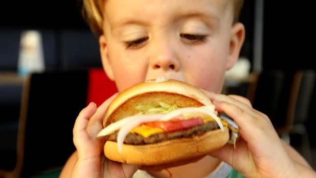 Kid eating hamburger. Fast food concept