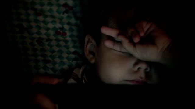 Kid face looking at tablet computer at night video