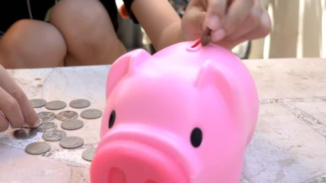 vidéos et rushes de main de gosse mettant les pièces de monnaie thaïlandaises de baht dans la tirelire rose - tirelire