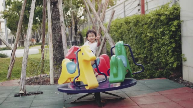 Kid Having Fun On Merry-Go-Round Asian baby boy spinning on the carousel at amusement park outdoor play equipment stock videos & royalty-free footage