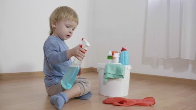 vidéos et rushes de enfant en danger s'asseyant près d'un seau avec des bouteilles en plastique avec des produits chimiques ménagers, le petit garçon pulvérise le détergent en verre sur le gant en caoutchouc sur le plancher dans la pièce - danger