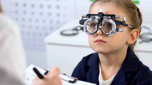 vidéos et rushes de enfant dans le cadre optique d'essai regardant le docteur prescrivant des lunettes, ophtalmologie - examen ophtalmologique