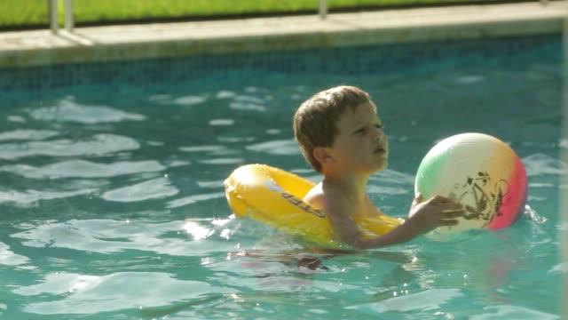 vídeos de stock e filmes b-roll de criança na piscina com um boia e um segurar num bola. jovem rapaz 5 anos de idade, a divertir-se durante as suas férias de verão férias - swim arms