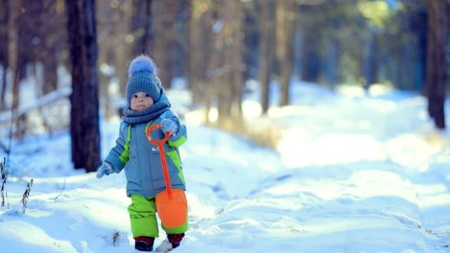 vídeos y material grabado en eventos de stock de niño está en el camino en el bosque de invierno. close-up - abrigo