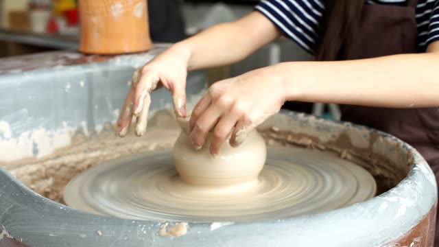 vídeos de stock e filmes b-roll de kid is working at pottery wheel slowly and molding a vase - teacher school solo