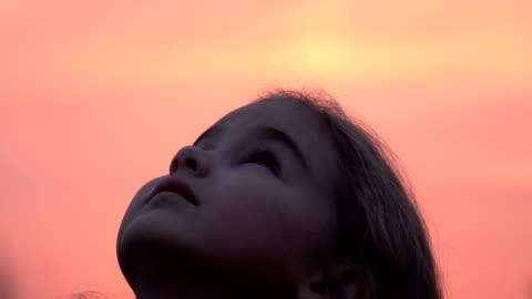 ragazzo che guarda il cielo nella natura. bambina che prega guardando il cielo viola con speranza, da vicino. - guardare in una direzione video stock e b–roll