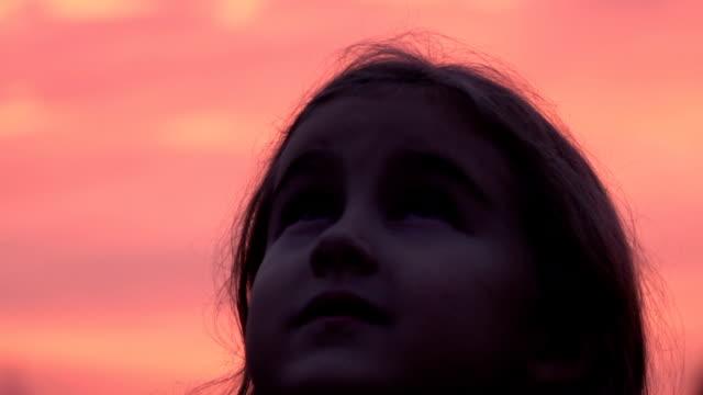 子供は自然に空を見上げてします。小さな女の子と、紫の空を見上げて祈ってクローズ アップ。 - 希望点の映像素材/bロール
