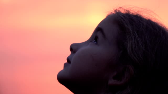 kid looking up at the sky in nature. little girl praying looking up at purple sky with hope, close-up. - бог стоковые видео и кадры b-roll