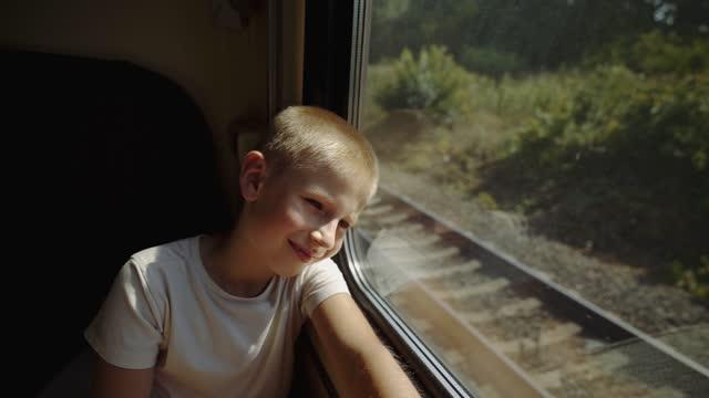 子供は電車の窓の外を見ます。少年は電車で旅行している。乗客の窓の外に対向貨物列車。 - 乗客点の映像素材/bロール