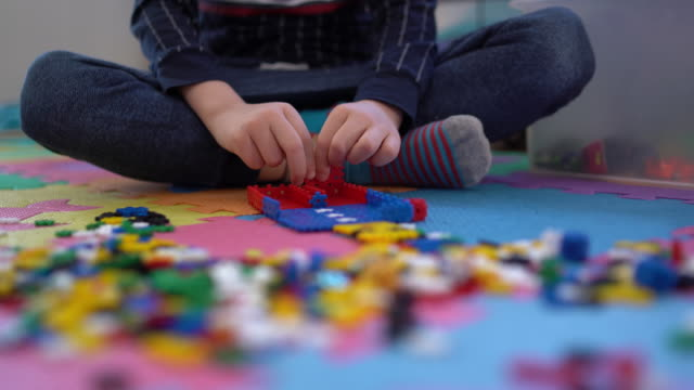 Kid Makes a Little Man of Puzzles - Closeup shot - Stock Video Kid is making little man of puzzles. Concept: creativity, creative development playroom stock videos & royalty-free footage