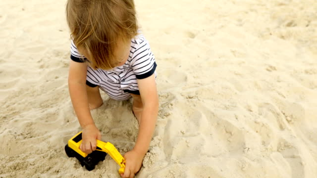kid playing raod works with toy excavatorin in sand