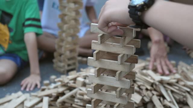 vídeos de stock e filmes b-roll de kid playing tower building game - material de construção